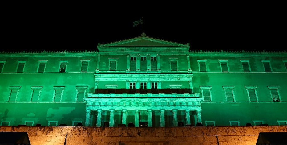 Presidential guards perform their ceremonial duties in front of the Greek parliament in Athens, Saturday, Nov. 5, 2016. The parliament was illuminated in green light to celebrate the entry into the U.N. Paris Climate Change agreement. (AP Photo/Yorgos Karahalis)