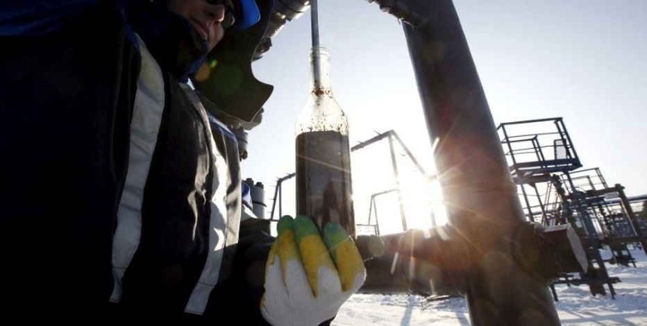 A worker takes oil samples from a well at the Gazpromneft-owned Yuzhno-Priobskoye oil field outside the West Siberian city of Khanty-Mansiysk, Russia, January 28, 2016. REUTERS/Sergei Karpukhin/File Photo