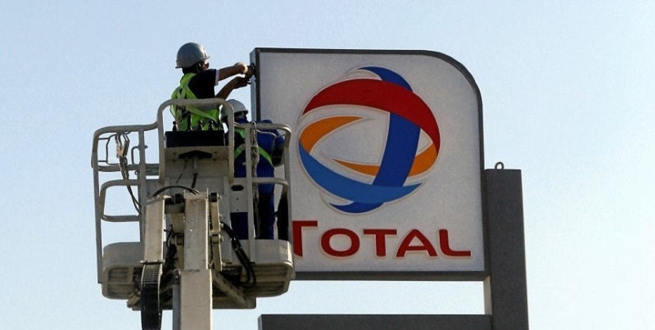 Workers fixing the logo for oil giant Total is seen at a petrol station in Cairo, Egypt, October 13, 2016. REUTERS/Amr Abdallah Dalsh
