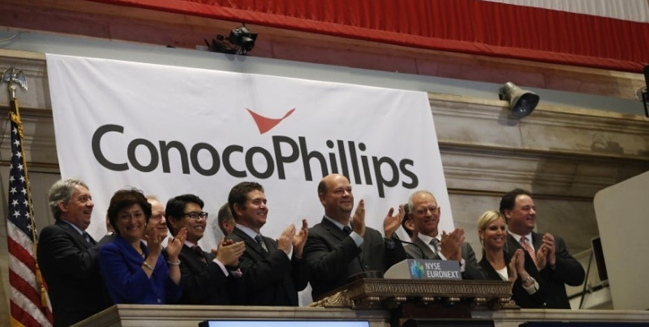 ConocoPhillips Chairman and Chief Executive Officer Ryan M. Lance (C) rings the closing bell at the New York Stock Exchange (NYSE), February 27, 2013. REUTERS/Brendan McDermid/File Photo