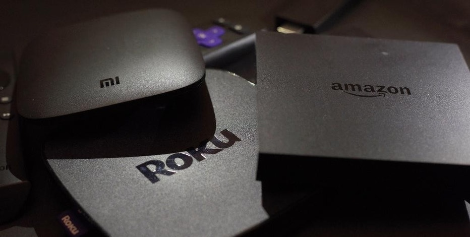 This Wednesday, Nov. 16, 2016 photo shows Xiaomi's Mi Box, left, the Roku Premiere, center, and the Amazon Fire TV streaming TV devices in New York.  Your streaming TV options just got better and cheaper. Features that once required a $100 device can now be had for as little as $30. A cheap device is fine for getting TV shows and movies from most popular services onto a big-screen TV, as long as it's a regular, high-definition set.(AP Photo)