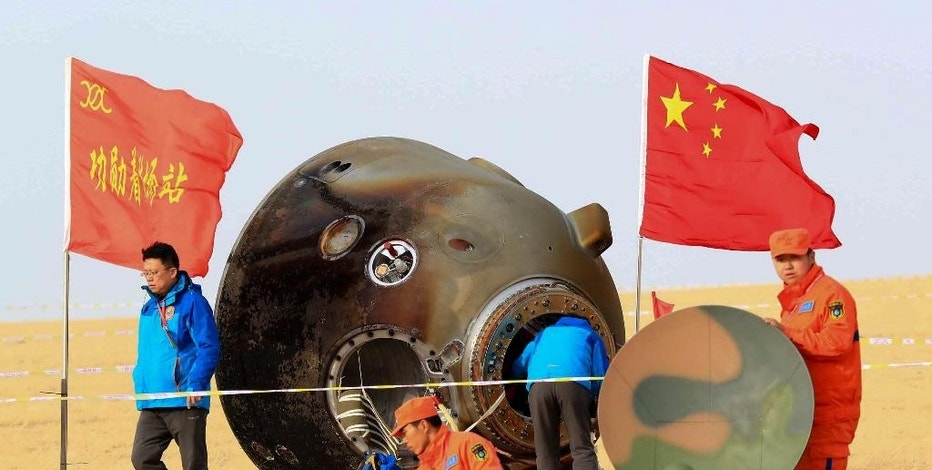 In this photo released by Xinhua News Agency, ground crew check on the re-entry capsule of Shenzhou 11 spacecraft after it landed in north China's Inner Mongolia Autonomous Region, Friday, Nov. 18, 2016. A pair of Chinese astronauts returned Friday from a monthlong stay aboard the country's space station, China's sixth and longest crewed mission and a sign of the growing ambitions of its rapidly advancing space program. (Li Gang/Xinhua via AP)