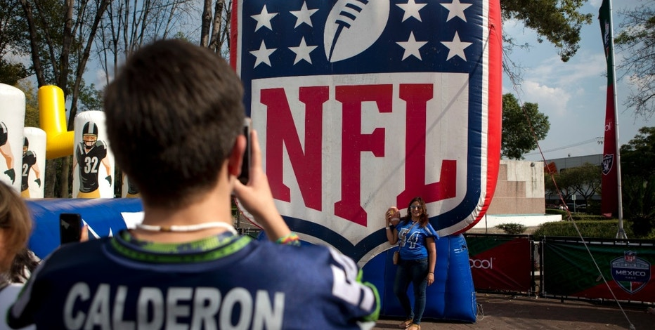 "In this Nov. 6, 2016 photo, fans take photos by the NFL logo set up at the third annual American Football Expo in Mexico City. Football, or ""futbol Americano,"" has a century-old tradition in Mexico and is one of the most popular sports in the country, where millions of fans follow the action on TV every Sunday. (AP Photo/Eduardo Verdugo)"