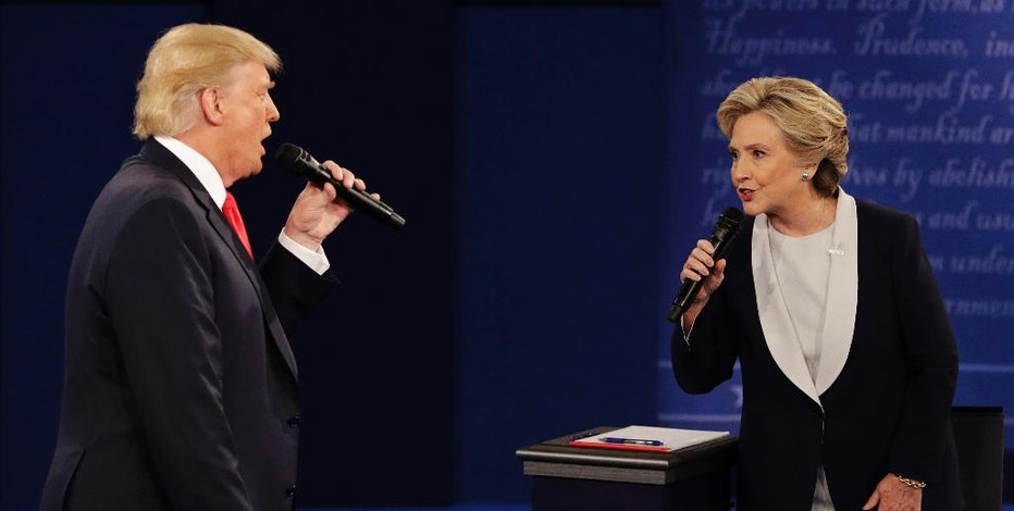 """FILE - In this Sunday, Oct. 9, 2016, file photo, Republican presidential nominee Donald Trump and Democratic presidential nominee Hillary Clinton speak during the second presidential debate at Washington University in St. Louis. A """"sophisticated"""" Russian propaganda campaign helped flood social media with fake news stories during the election season, according to a new report in The Washington Post. The Post says the goal was to punish Hillary Clinton, help Donald Trump, and undermine faith in American democracy. (AP Photo/John Locher, File)"""
