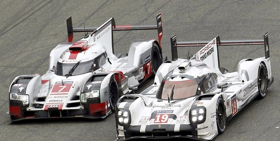Nick Tandy of Britain drives his Porsche 919 Hybrid number 19 (R) ahead the Audi R18 e-tron quattro number 7 driven by Marcel Fassler of Switzerland, during the Le Mans 24 Hours sportscar race in Le Mans, central France June 14, 2015. REUTERS/Regis Duvignau/File Photo