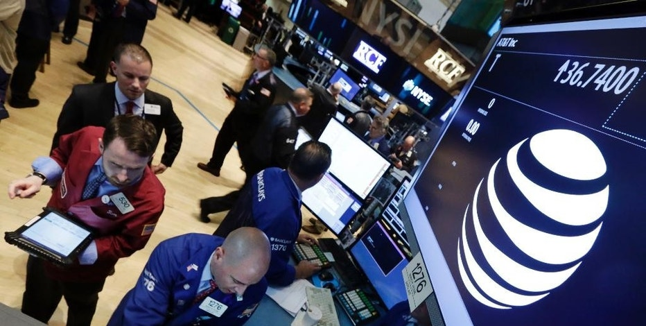 FILE - In this Monday, May 19, 2014, file photo, traders gather at the post that handles AT&T on the floor of the New York Stock Exchange. There are already a few online services that aim to replace cable, but they don't have many users yet. AT&T's DirecTV hopes to change that. (AP Photo/Richard Drew, File)
