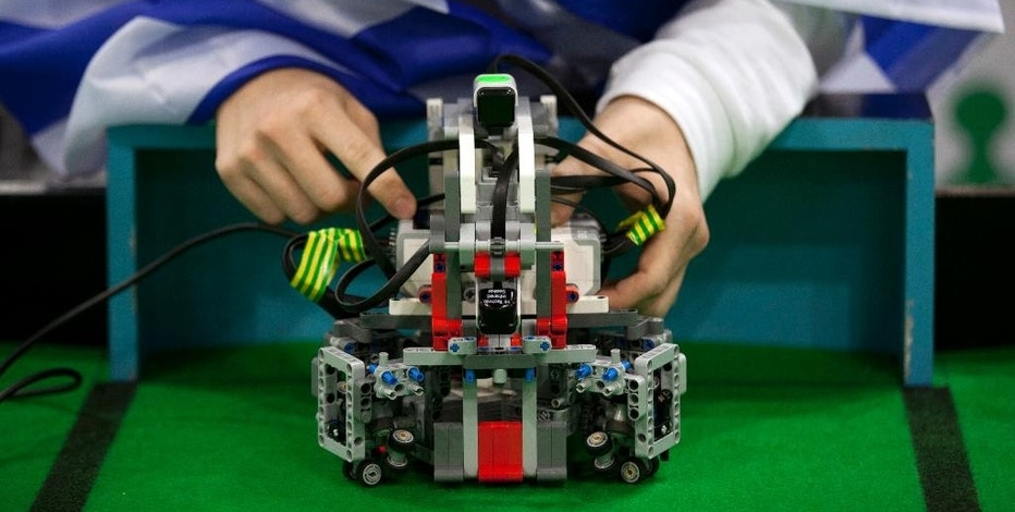 In this Sunday, Nov. 27, 2016 photo, a participant from Greece gets his robot ready for a game of soccer at the World Robot Olympiad in New Delhi, India. The weekend games brought more than 450 teams of students from 50 countries to the Indian capital. (AP Photo/Tsering Topgyal)