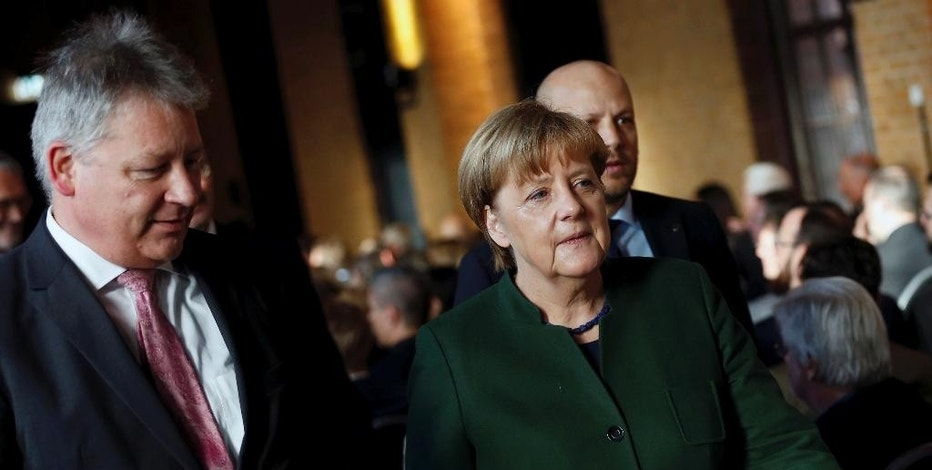 German Chancellor Angela Merkel,right, and the President of the German Federal Intelligence Agency (BND) Bruno Kahl attend a ceremony for the 60th anniversary of the founding of the BND in Berlin, Germany, Monday Nov. 28, 2016. (Hannibal Hanschke/Pool Photo via AP)