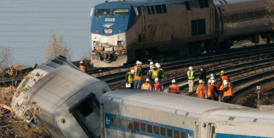 FILE - In a Dec. 1, 2013 file photo, an Amtrak train, top, traveling on an unaffected track, passes a derailed Metro North commuter train, in the Bronx borough of New York. Officials are standing on a curve in the tracks where the Metro North train derailed. Federal regulators said Monday, Nov. 28, 2016. The nation's three busiest commuter railroads, The Long Island Rail Road, New Jersey Transit and Metro-North, continue to lag behind their smaller West Coast counterparts in installing sophisticated train-control technology that's seen as an antidote to crashes involving speeding and other human factors. (AP Photo/Mark Lennihan, File)