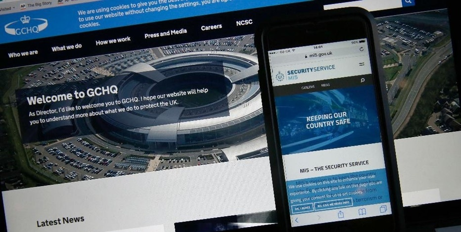 This photo-illustration shows the web flash pages for GCHQ, the British governments communications and electronic surveillance headquarters, and The Security Service (MI5), the governments internal security service, on a computer and smartphone in London, Friday, Nov. 25, 2016. After months of wrangling, Parliament has passed a contentious new snooping law that gives authorities — from police and spies to food regulators, fire officials and tax inspectors — powers to look at the internet browsing records of everyone in the country. (AP Photo/Alastair Grant)