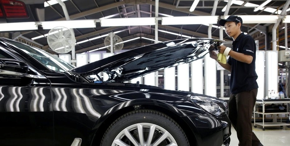 A worker closes the hood on a locally assembled new BMW 7 Series on the production line at a Gaya Motor assembly plant in Jakarta, Indonesia November 30, 2016.   REUTERS/Darren Whiteside