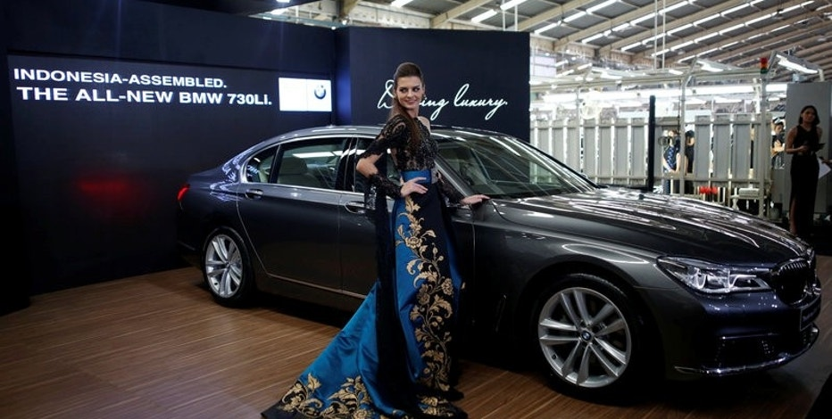 A model poses next to a BMW 7 Series car assembled locally during a media launch at a Gaya Motor assembly plant in Jakarta, Indonesia November 30, 2016.   REUTERS/Darren Whiteside