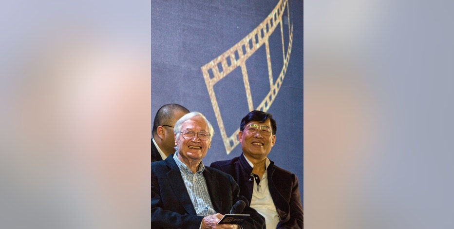 """American film producer Roger Corman, left, attends a news conference to announce the co-production between Chinese online video site iQIYI and Sony Pictures in Beijing, China, Thursday, Dec. 1, 2016. The 90-year-old American producer of films including """"The St. Valentine's Day Massacre"""" and """"Attack of the 50 Foot Cheerleader"""" will lead a team of young Chinese filmmakers and act as producer on a sci-fi film made for viewing on the internet or mobile phone called """"Invasion."""" (AP Photo/Ng Han Guan)"""