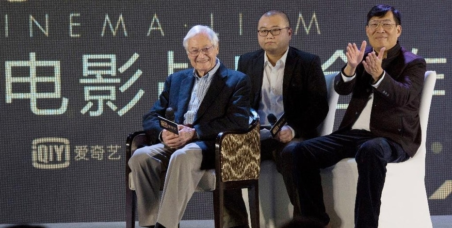 """American film producer Roger Corman, left, attends a news conference to announce co-production between Chinese online video site iQIYI and Sony Pictures in Beijing, China, Thursday, Dec. 1, 2016. The 90-year-old American producer of films including """"The St. Valentine's Day Massacre"""" and """"Attack of the 50 Foot Cheerleader"""" will lead a team of young Chinese filmmakers and act as producer on a sci-fi film made for viewing on the internet or mobile phone called """"Invasion."""" (AP Photo/Ng Han Guan)"""
