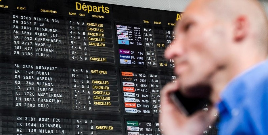 FILE - In this Wednesday, May 27, 2015, file photo, a passenger makes a phone call as he walks by a flight information board at Brussels Airport in Zaventem, Belgium. You don't have to pay a fortune to use your phone abroad, but you need to plan ahead. Getting a local plan when you arrive is the most economical choice, but it's not practical for many people. (AP Photo/Geert Vanden Wijngaert, File)