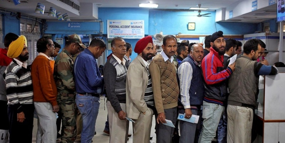 FILE PHOTO - People queue as they wait for their turn to exchange or deposit their old high denomination banknotes in Jammu, November 24, 2016. REUTERS/Mukesh Gupta/File Photo