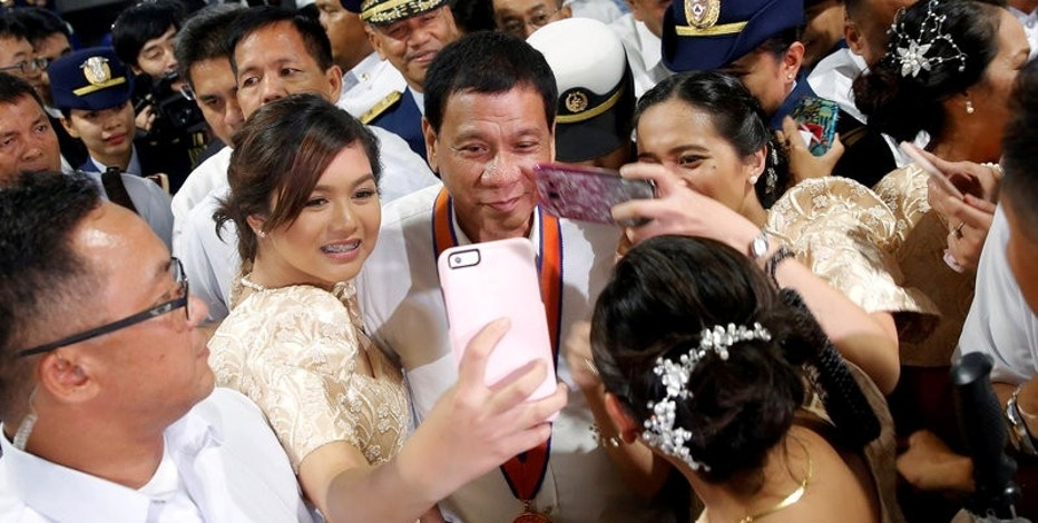 FILE PHOTO - Philippines President Rodrigo Duterte has his pictures taken with women as they attend the ceremony marking the anniversary of the Philippines Coast Guard in Manila, Philippines, October 12, 2016.   REUTERS/Damir Sagolj/File Photo