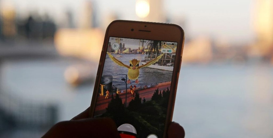 "FILE - In this July 25, 2016, file photo, a fan maneuvers his smartphone as he plays ""Pokemon Go"" in Hong Kong. ""Pokemon Go"" is among Google's most-trending searches of 2016. The search engine giant released its year end trending searches list on Dec. 14, 2016. (AP Photo/Kin Cheung, File)"