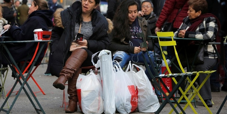 A woman sits in Herald Square with bags of shopping during Black Friday sales in Manhattan, New York, U.S., November 25, 2016.  REUTERS/Andrew Kelly