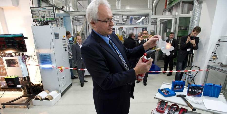 Company HE3DA President Jan Prochazka shows qualities of a new battery during the  official start of a battery production line in Prague, on Monday, Dec. 19, 2016. The new battery is based on nanotechnology and is supposed to be be more efficient, long-lasting, cheaper, lighter and above all safer. The battery is designed to store energy from renewable electric sources and cooperate with smart grids. Next planned type will be suitable for electric cars. (Michal Kamaryt /CTK via AP)