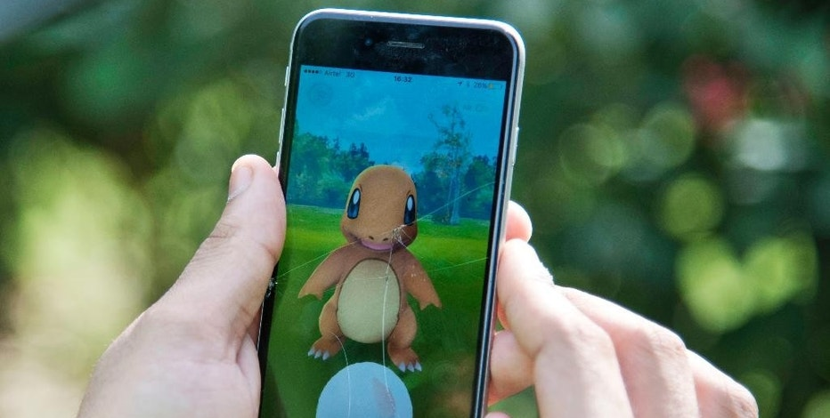 FILE - In this Friday, July 22, 2016 file photo, a Pokemon Go player attempts to catch a Charmander character in New Delhi, India. The popular augmented reality mobile game is coming to the Apple Watch, squashing rumors that the game's maker was scrapping such plans. Plans for the watch version had been announced at Apple's iPhone launch event in September. (AP Photo/Thomas Cytrynowicz)