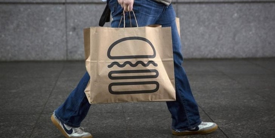 A man carries away bags of Shake Shack in New York January 30, 2015. REUTERS/Andrew Kelly