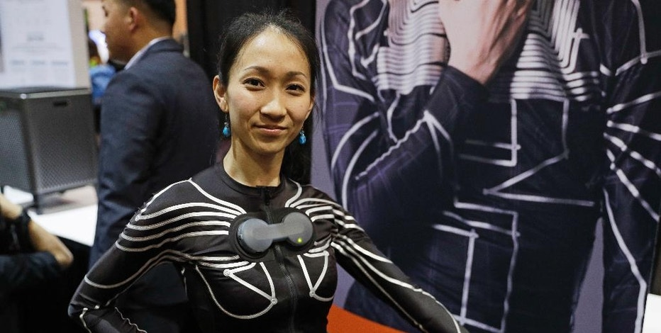 A woman wears an e-skin shirt at the Xenoma booth during CES Unveiled before CES International, Tuesday, Jan. 3, 2017, in Las Vegas. The smart shirt enables motion and gesture tracking technology for virtual reality games, fitness and healthcare. (AP Photo/John Locher)