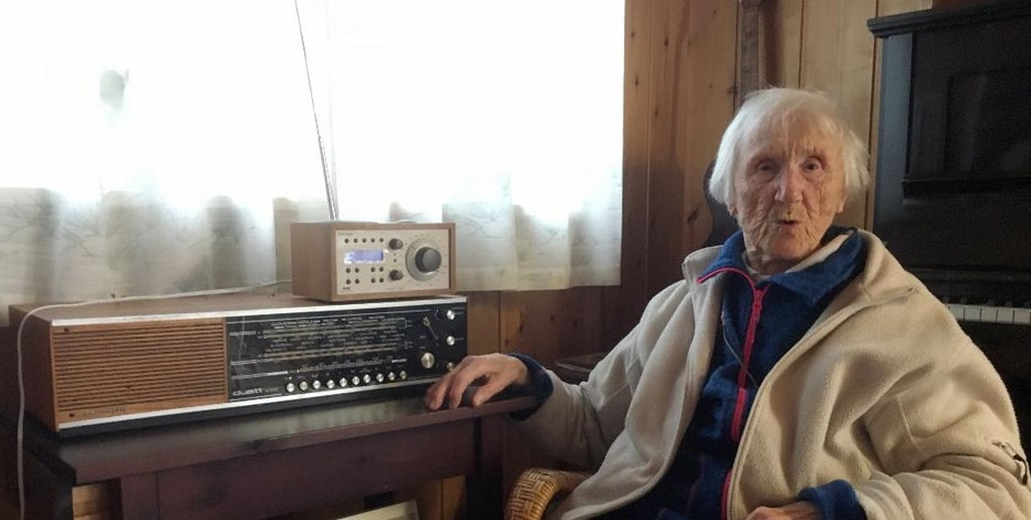 In this photo taken on Sunday, Jan. 8, 2017, 98-year-old Judith Haaland sits next to her decades-old radio set in Stavanger, Norway. In a move likely to be watched closely by other nations, the Norwegian government will begin shutting off the FM signal on Wednesday, Jan. 11, 2017. By the end of the year, national networks will be available only on Digital Audio Broadcast, or DAB. (AP Photos/Mark Lewis)