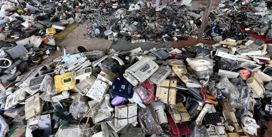 In this Friday, Jan. 13, 2017 photo, a customer browses through used items at a flea market on the outskirts of Jakarta, Indonesia. The waste from discarded electronic gadgets and electrical appliances has increased by two-thirds in East Asia over five years, posing a growing threat to health and the environment unless proper disposal becomes the norm. The United Nations University says China is the biggest culprit with its electronic waste more than doubling. (AP Photo/Tatan Syuflana)