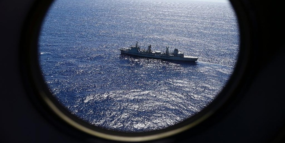 FILE - In this March 31, 2014 file photo, HMAS Success scans the southern Indian Ocean, near the coast of Western Australia, as a Royal New Zealand Air Force P3 Orion flies over, while searching for missing Malaysia Airlines Flight MH370. Nearly three years after a Malaysian airliner vanished, it's still possible, if unlikely, for a plane to disappear. But that's changing with new satellites that will soon allow flights to be tracked in real time over oceans. (AP Photo/Rob Griffith, File)