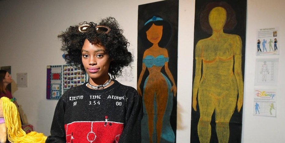 "In this Friday, Dec. 9, 2016, photo, Ajani Russell poses with her artwork ""Female Figures"" prior to the Animated Women symposium at California Institute of the Arts, in Valencia, Calif. The California Institute of the Arts was created partly by Walt Disney's desire to bring more top-flight animators into the profession. And it has during its 47 years, though for a long time almost all were men. Now, nearly three-quarters of CalArts' more than 250 animation students are women, and there's a new goal: Ensure that when they land jobs, they get to draw female characters reflective of the real world and not just the nerds, sex bombs, tomboys or ugly villains who proliferate now. (AP Photo/Mark J. Terrill)"
