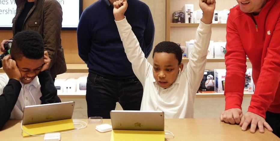 FILE - In this Wednesday, Dec. 9, 2015, file photo, Jaysean Erby raises his hands as he solves a coding problem as Apple CEO Tim Cook watches from behind at an Apple Store, in New York, as Apple hosted Hour of Code events around the world as part of Computer Science Education Week. Despite loudly touted efforts, the tech industry is making very little progress in diversifying its workforce, especially in technical and leadership positions. Companies are spending a lot of time and money on improving diversity, from outreach at high schools and historically black colleges to internship and mentoring programs to sponsorships for coding boot camps to bias training and support groups. So far, to little avail. (AP Photo/Mark Lennihan, File)