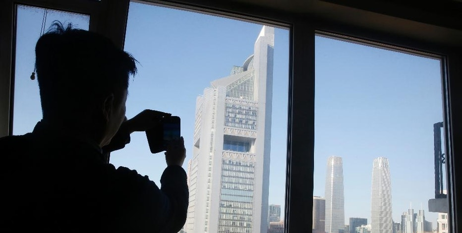 In this Jan. 9, 2017 photo, Zou Yi snaps a photo of the central business district, a daily ritual he has performed over four years to document the city's air quality, from his apartment in Beijing. There is no quick fix to the Chinese capital's dirty skies, so Beijing residents are finding ways to cope with and adapt to the air pollution. In doing so, some residents are coming up with technological innovations they hope will make people more aware of the air they are breathing in around the world. (AP Photo/Ng Han Guan)