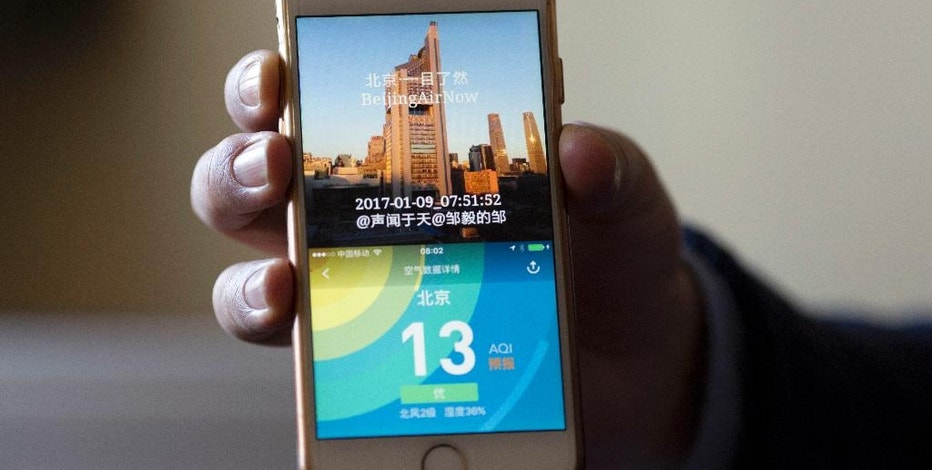In this Jan. 9, 2017 photo, Zou Yi shows the air quality information he shares on line from a snap shot taken daily from his apartment in Beijing. There is no quick fix to the Chinese capital's dirty skies, so Beijing residents are finding ways to cope with and adapt to the air pollution. In doing so, some residents are coming up with technological innovations they hope will make people more aware of the air they are breathing in around the world. (AP Photo/Ng Han Guan)