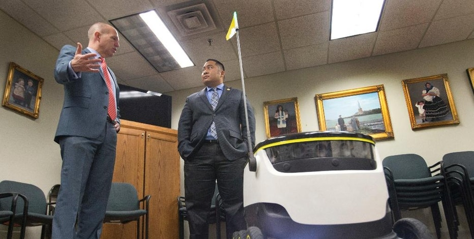 Chairman of the House Transportation Committee, Del. Ron Villanueva, R-Chesapeake, right, speaks with lobbyist, David Catania, during a demonstration of the Starship Technologies robot at the Capitol in Richmond, Va., Wednesday, Jan. 25, 2017. State lawmakers have partnered with European company Starship Technologies on bills that would allow Virginia cities to join two others in the U.S. and many across Europe where the company is testing the robots. Much like big-time retailers' attempts at drone deliveries, the robots aim to revolutionize the way people get their parcels.(AP Photo/Steve Helber)