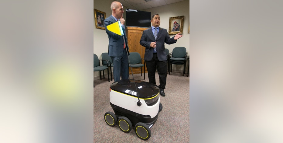 Chairman of the House Transportation Committee, Del. Ron Villanueva, R-Chesapeake, right, speaks with lobbyist, David Catania, during a demonstration of the Starship Technologies robot at the Capitol in Richmond, Va., Wednesday, Jan. 25, 2017. State lawmakers have partnered with European company Starship Technologies on bills that would allow Virginia cities to join two others in the U.S. and many across Europe where the company is testing the robots. Much like big-time retailers' attempts at drone deliveries, the robots aim to revolutionize the way people get their parcels. (AP Photo/Steve Helber)
