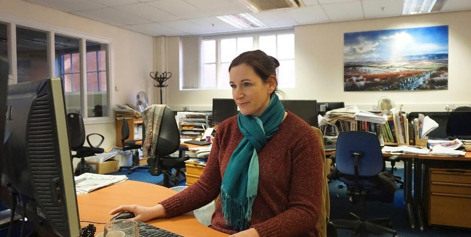 In this photo dated Saturday, Jan. 14, 2017, journalist Julia Breen works on a story in the newsroom of The Northern Echo newspaper in Darlington, England. The newspaper's journalists are among scores of reporters who have been spied on by British police over the past 5 years, according to court documents, although Cleveland Police issued a statement to deny allegations. (AP Photo/Raphael Satter)
