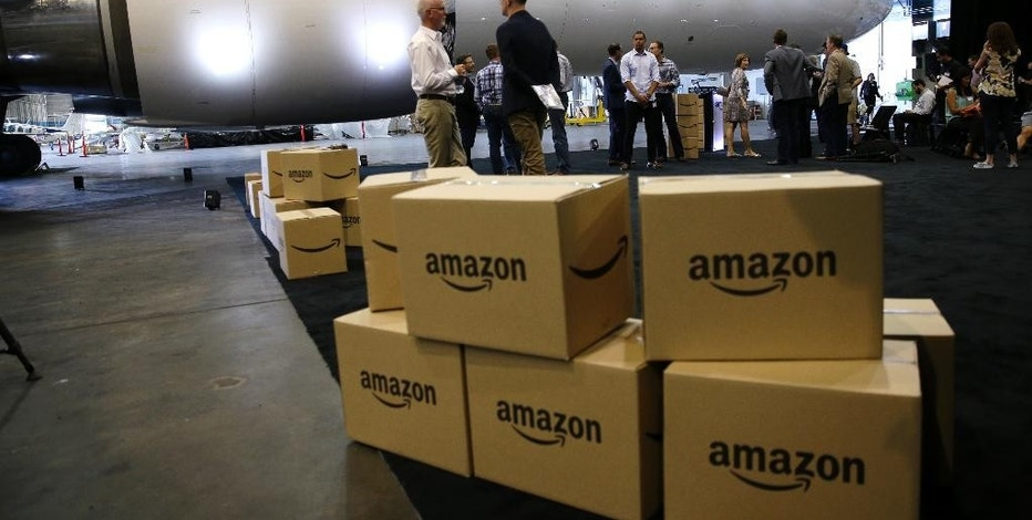 "FILE - In this Thursday, Aug. 4, 2016, file photo, Amazon.com boxes are shown stacked near a Boeing 767 Amazon ""Prime Air"" cargo plane on display  in a Boeing hangar in Seattle. Amazon's announcement on Monday, Jan. 30, 2017, of a new air cargo hub in Kentucky is the latest way the e-commerce retailer is dipping its toe, or perhaps whole foot, into building out its shipping and logistics unit. If successful, the move ultimately means lower costs for Amazon but it could eventually pit Amazon against package deliverers like FedEx and UPS. (AP Photo/Ted S. Warren, File)"