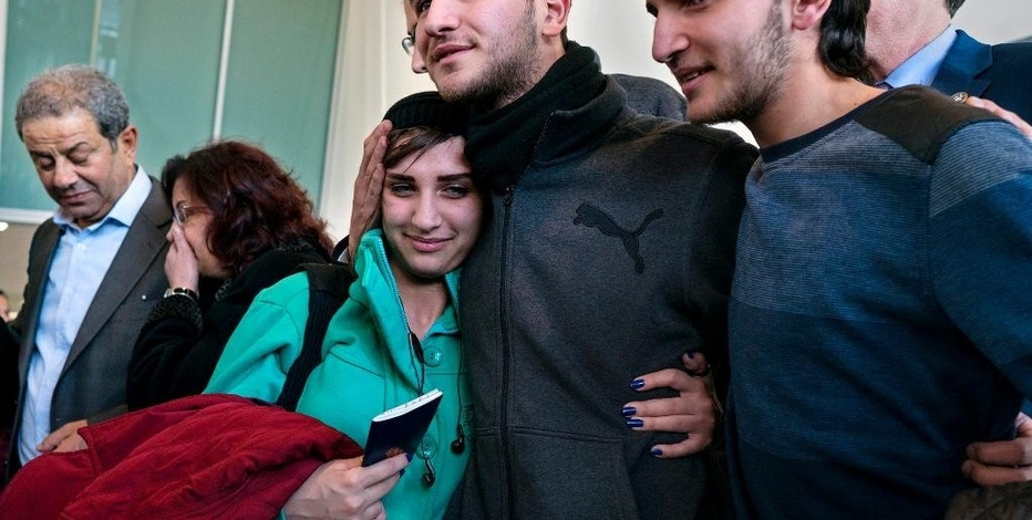 Tawfik Assali, 21, center, of Allentown, Pa., embraces his sister Sarah Assali, 19, upon her and other family members' arrival from Syria at Terminal at John F. Kennedy International Airport in New York, Monday, Feb. 6, 2017. Right is Mathew Assali, 17, who arrived today. Attorneys said Dr. Assali's brothers, their wives and their two teenage children returned to Syria after they were denied entrance to the United States on Jan. 28 although they had visas in hand after a 13-year effort. (AP Photo/Craig Ruttle)