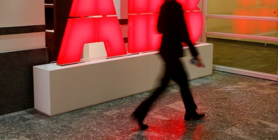 A woman walks past the logo of Swiss power technology and automation group ABB ahead of a news conference to present the company's full-year results in Zurich, Switzerland February 8, 2017. REUTERS/Arnd Wiegmann