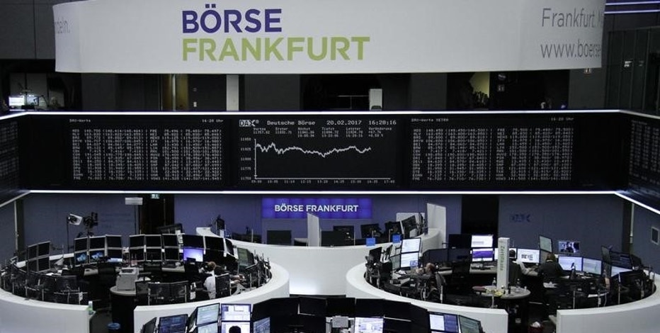 Traders work at their desks in front of the German share price index, DAX board, at the stock exchange in Frankfurt, Germany, February 20, 2017. REUTERS/Staff/Remote