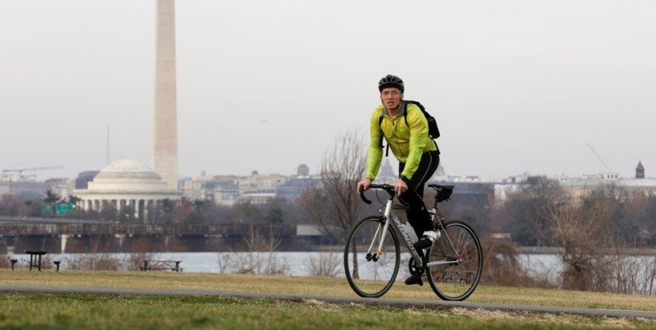 A man rides his bicycle during unseasonably warm weather in Washington, U.S., February 22, 2017.