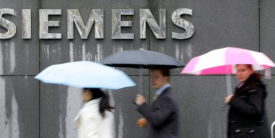 FILE PHOTO: People covered with umbrellas walk next to a Siemens building in Munich, Germany, November 13, 2008.  REUTERS/Michaela Rehle/File Photo