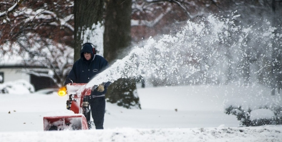 A man uses a snow blower to remove snow from the sidewalk on Midland Street in Bay City on Monday, Dec. 12, 2016, as a winter storm pushed eastward. (Jacob Hamilton/The Bay City Times via AP)