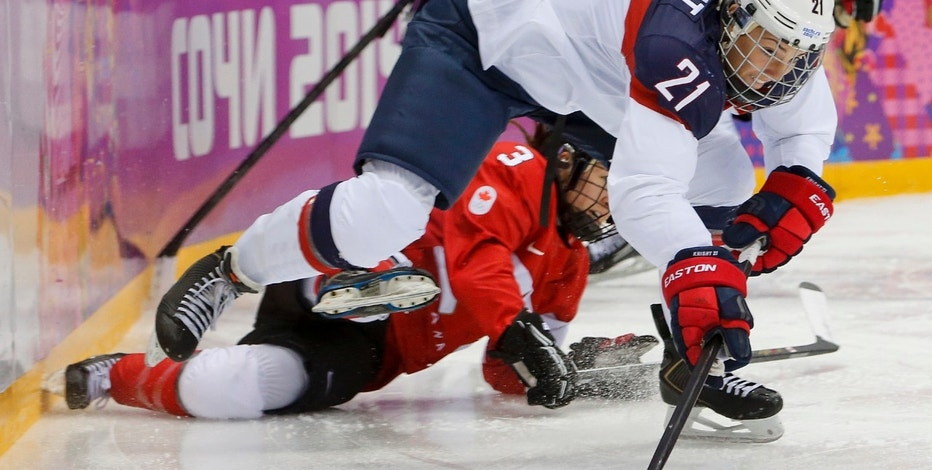 """FILE - In this Feb. 20, 2014, file photo, United States' Hilary Knight passes the puck against Canada during the first period of the women's gold medal ice hockey game at the Winter Olympics in Sochi, Russia. After players threatened Wednesday, March 15, 2017, to boycott the upcoming world hockey championships over a wage dispute, USA Hockey said it will """"field a competitive team"""" for the International Ice Hockey Federation Women's World Hockey Championship that begins March 31 in in Plymouth, Mich. """"We're unanimously united as a player pool,"""" Knight said. """"Good luck getting a suitable No. 1 competition to represent our country on a world stage. I kind of dare them. It's tough."""" (AP Photo/Mark Humphrey, File)"""