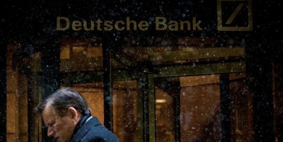 A man walks past the Deutsche Bank offices during a snow storm in Manhattan's financial district in New York January 21, 2014.   REUTERS/Brendan McDermid/File Photo