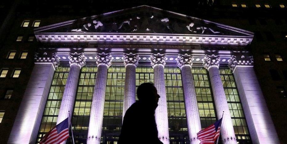 FILE PHOTO: A commuter passes by the New York Stock Exchange (NYSE) in the financial district in New York City, U.S., February 7, 2017. REUTERS/Brendan McDermid/File Photo