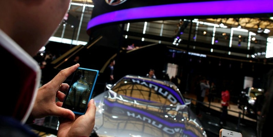 FILE PHOTO: A man takes pictures of a Hyundai car during the 15th Shanghai International Automobile Industry Exhibition in Shanghai April 21, 2013. REUTERS/Carlos Barria/File Photo