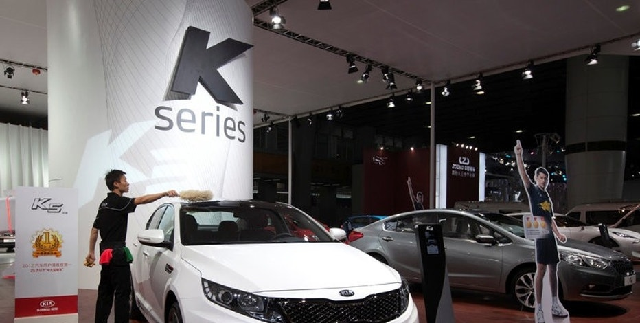 FILE PHOTO: A worker cleans a KIA K5 during the media preview of the 10th China International Automobile Exhibition in Guangzhou November 22, 2012. REUTERS/Tyrone Siu/File Photo