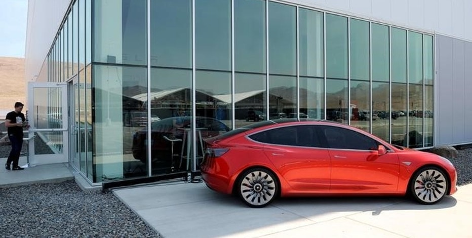 A prototype of the Tesla Model 3 is on display in front of the factory during a media tour of the Tesla Gigafactory which will produce batteries for the electric carmaker in Sparks, Nevada, U.S. July 26, 2016.  REUTERS/James Glover II/File Photo
